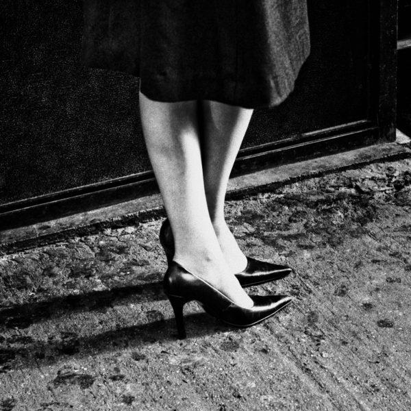 This is a square formatted black and white photo showing the calves and high heeled pumps of a woman. She is wearing a black pencil skirt that falls below the knees and her legs are slightly crossed. The concrete sidewalk looks dirty. It was taken in 2009 by Michael Penn, however, by looking it's impossible to tell what year it is.