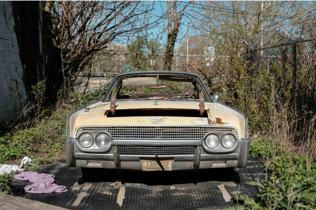 Colored Photograph of an abandoned car in lot.