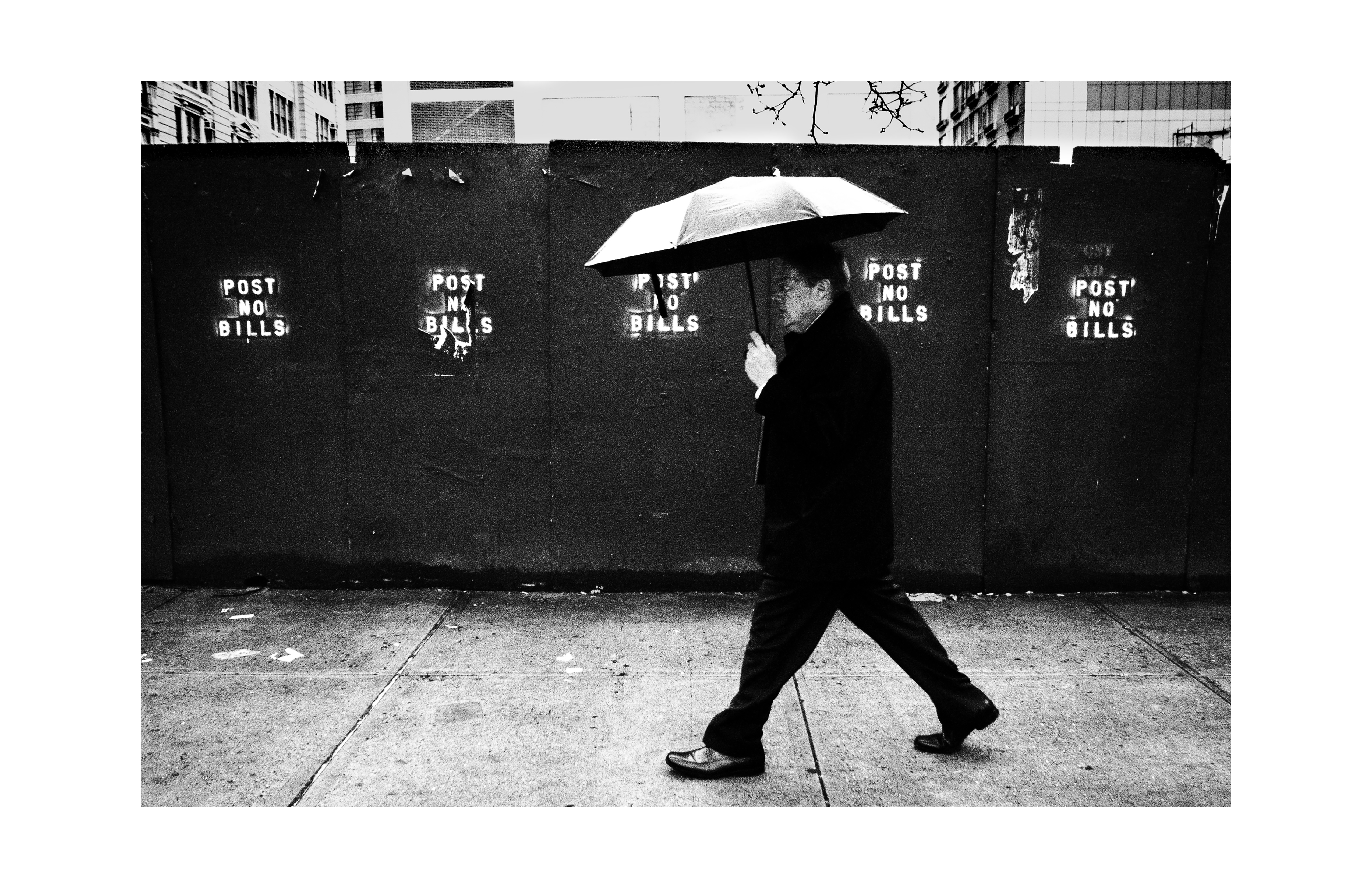 Photograph of man walking in the rain with his umbrella